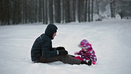 Father with small kid playing on snow together
