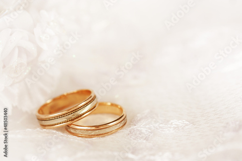 Two golden wedding rings with seamless flower decorations.