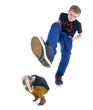 Großer Teenager tritt kleinen Teenager mit dem Fuß