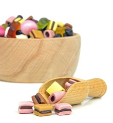 A wooden scoop and bowl of mixed sweets