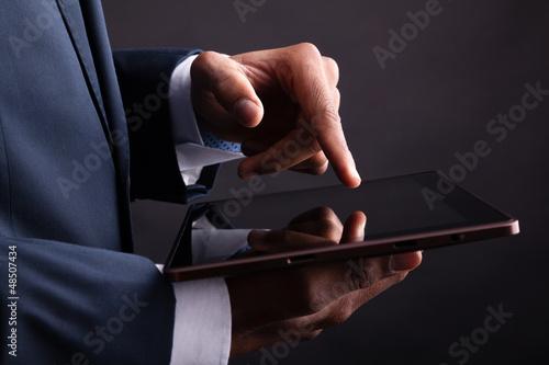 Closeup of businessman holding digital tablet on black backgroun