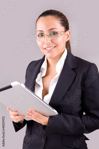 Young smiling business woman with tablet computer on grey backgr
