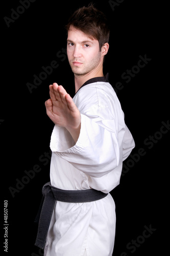Young man practicing martial arts over black background