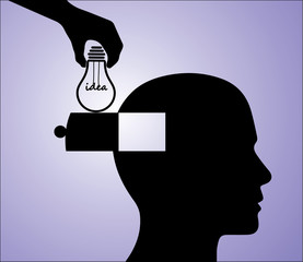 A hand inserting an light bulb idea into a man's head