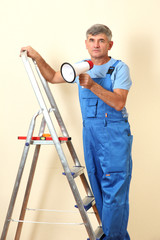 Construction superintendent directs repair sitting on ladder