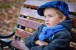 Portrait of boy on bench in park