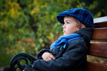 Portrait of boy on bench in park