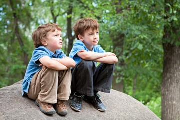 Two brothers sitting on rock