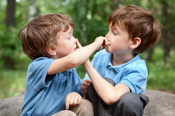 Two brothers click on  nose