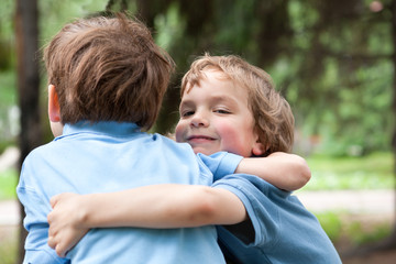 Two brothers hugging in park