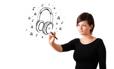 Young girl drawing headphone and musical notes
