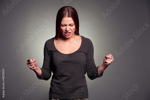 angry young woman over dark background
