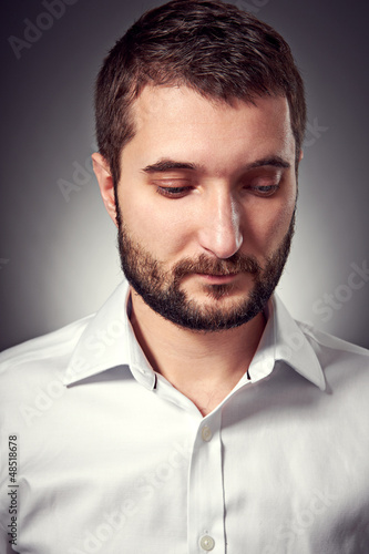 handsome man with beard looking down