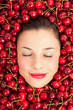 Young girl smiling portrait surrounded by cherries.