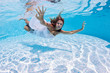 Underwater girl portrait with white dress in swimming pool.