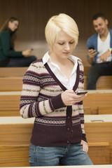Zwei Studentinnen und ein Student telefonieren und schreiben SMS