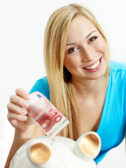 Woman is happy to save money in her piggy bank