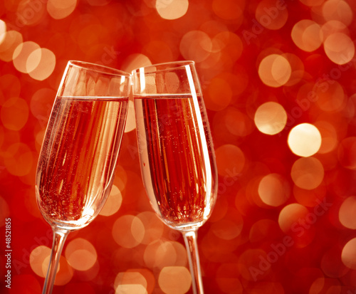 Two glasses of champagne with lights in the background.