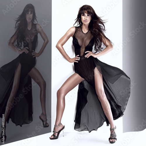 Fashionable young woman posing in long black dress