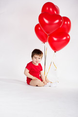 Little baby boy with red balloons. Valentines day