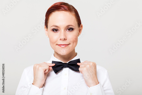 beautiful young waitress holding bow tie and smiling