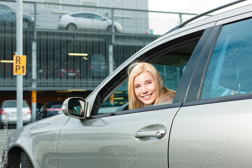 Woman back her car on a parking level