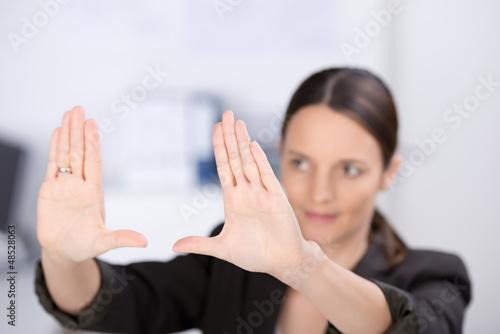 geschäftsfrau bildet einen rahmen mit ihren händen