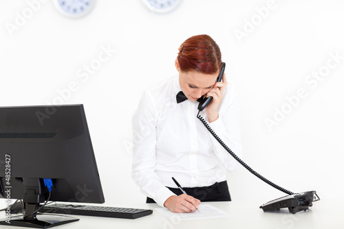 modern hotel receptionist talking on the phone at reception