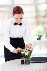 elegant young waitress setting up restaurant table