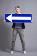 Pleased man holding horizontal direction arrow sign.
