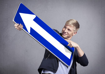 Close up of smiling man holding direction arrow sign.