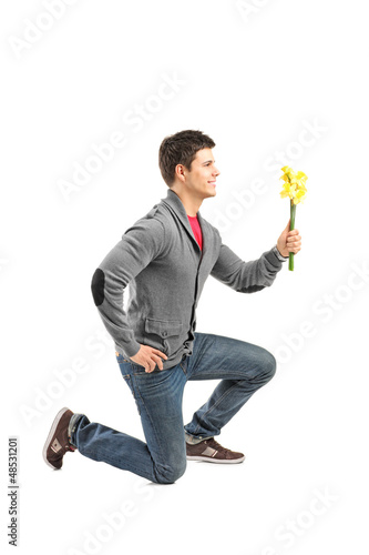 A male kneeling and holding a daffodil flower