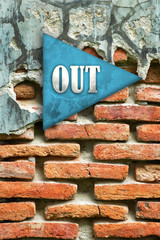 out sign on brick wall