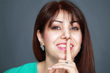 Smiling woman with finger on lips
