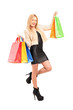 Full length portrait of a beautiful young woman holding shopping