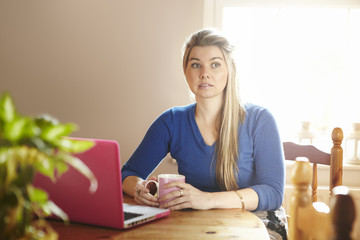 Young woman sitting at table with laptop looking confused