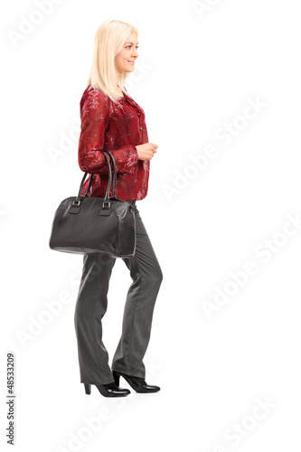 Full length portrait of a blond woman standing in profile