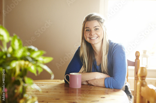 Young woman sitting at table smiling