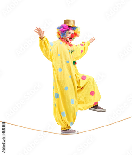 Full length portrait of a happy male clown walking on a rope