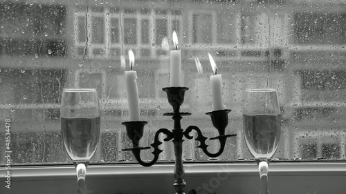 Lighted candles and raindrops on the window black and white