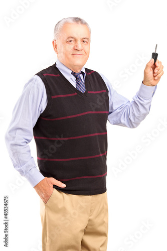 Satisfied mature man holding a car key