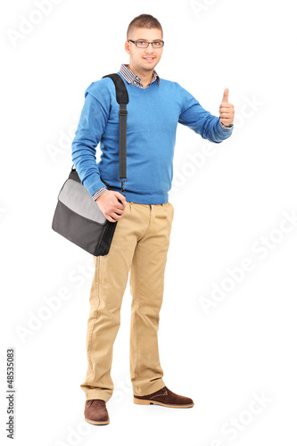 Full length portrait of a young man with a shoulder bag giving a