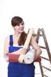 Junge Frau mit Tapetenrollen und Leiter.