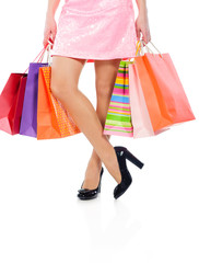 Woman legs with colorful shopping bags