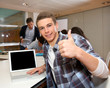 Student with laptop showing thumb up
