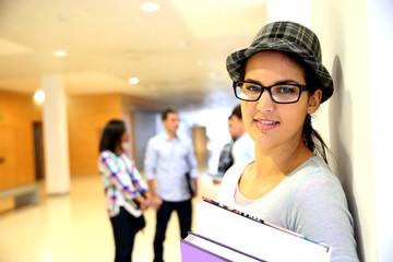 Trendy teen girl standing in school building
