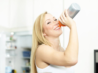 Active woman drinking water bootle in the kitchen