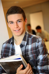Student boy in class holding books