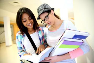 Teenagers in school hallway reading books