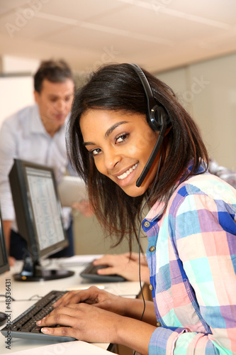 Portrait of cheerful young woman with headset on